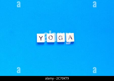 The word YOGA written in wooden letterpress type on a blue background. top view. flat layout. - Stock Photo