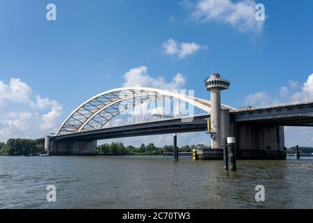 Van Brienenoord Bridge in Rotterdam over the river Nieuwe Maas seen from the north bank on the east side. The two arch bridges, part of the A16 motorw - Stock Photo