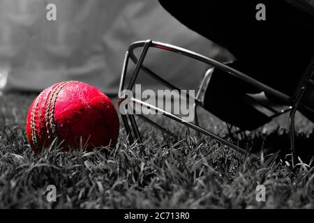 Cricket halmet and a ball on a green grass. Helmet protects batsman from fast balls which may otherwise cause harm to playing person.Black and white photo - Stock Photo