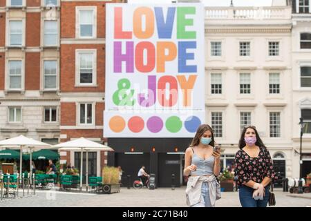 Two women wearing protective face masks walk beneath a mural by graphic artist Anthony Burrill, in Covent Garden, London, after the lifting of further coronavirus lockdown restrictions in England. - Stock Photo