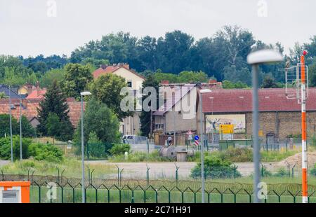 02 July 2020, Brandenburg, Schönefeld/Ot Selchow: Residential and commercial buildings in the village near the fence at the end of the northern runway of the airport. Photo: Soeren Stache/dpa-Zentralbild/ZB - Stock Photo