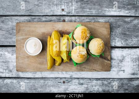 Three mini burgers with beef patty, french fries and mayonnaise on wooden board. Shabby aged table background. Unusual food serving. Fast food and unhealthy lifestyle. - Stock Photo