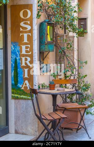 The front terrace of local osteria featuring a typical Italian table and chairs and a cute setting in Montalcino, Italy. - Stock Photo