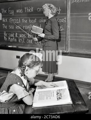 1950s READING TEACHER POINTING TO WORDS ON BLACKBOARD AS GIRL STUDENT SITTING AT HER DESK FOLLOWS ALONG IN TEXTBOOK - s3733 HAR001 HARS COMMUNICATION LIFESTYLE SATISFACTION FEMALES COPY SPACE HALF-LENGTH LADIES PERSONS INSPIRATION MIDDLE-AGED B&W SCHOOLS POINTER GRADE MIDDLE-AGED WOMAN HIGH ANGLE TEXTBOOK ALONG INSTRUCTOR PROGRESS WORDS OCCUPATIONS PRIMARY CONCEPTUAL EDUCATOR ANONYMOUS BRAIDS EDUCATING EDUCATORS GRADE SCHOOL GROWTH INSTRUCTORS JUVENILES PIGTAILS SCHOOL TEACHES BLACK AND WHITE CAUCASIAN ETHNICITY HAR001 OLD FASHIONED