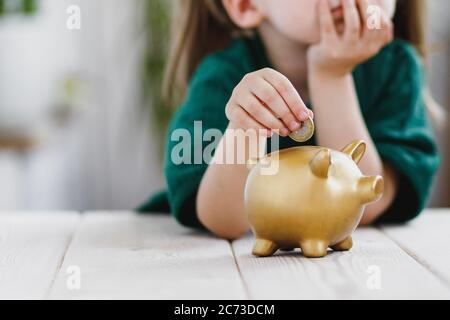 Little girl in green dress thinking about her money spending and putting a coin into a piggy bank. Money saving concept - Stock Photo