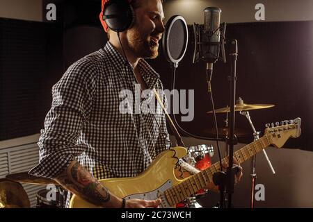 awesome caucasian musician play electric guitar and sing in recording studio. man preparing, practicing before music performance, before concert. musi