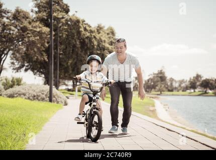Boy learning to ride a bicycle with his father in the park by the lake. Father and son having fun together on the bikes. Happy family, outdoors activi