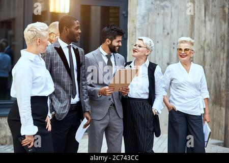 Group of businessmen move outdoor. In centre caucasian brunet bearded man in stylish grey suit smile broadly, keep papier. Woman near smile red lips, - Stock Photo