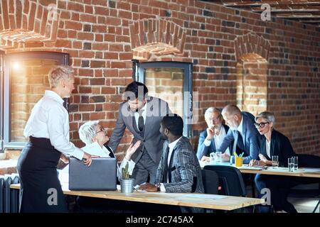 In the foreground two blonde caucasian women, caucasian bearded brunette man, african man discuss. On the background two blonde caucasian men and one