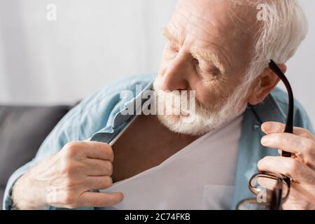 Selective focus of senior man holding eyeglasses and feeling heat at home - Stock Photo