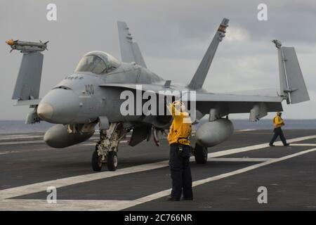 A U.S. Marine Corps F/A-18C Super Hornet assigned to the Death Rattlers of Marine Fighter Attack Squadron 323, is positioned on the flight deck of the Nimitz-class aircraft carrier USS Nimitz during dual-carrier operations with the USS Ronald Reagan June 28, 2020 in the Philippine Sea. Stock Photo