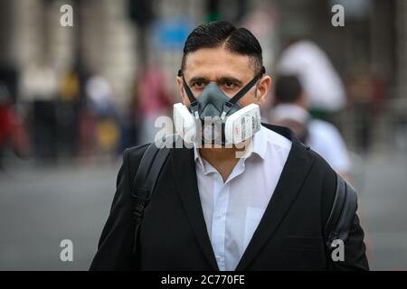 Westminster, London, UK. 14th July, 2020. A man takes no chances by wearing a filtered face mask in Westminster. Face masks ar already mandatory on public transport, and a also required in shops and supermarkets from July 24th in England. Credit: Imageplotter/Alamy Live News - Stock Photo
