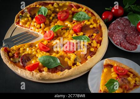 Slice of pizza with cherry and basil on a black background. Ingredients for preparing national Italian food. Tasty freshly prepared pizza with cherry - Stock Photo