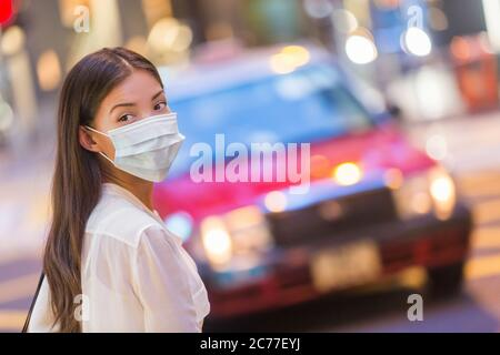 Flu disease virus spreading protection mask protective against influenza viruses and diseases. Asian woman wearing surgical mask on face in public spa - Stock Photo