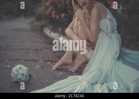 portrait of a lonely bride, in a white dress, sitting on the pavement, against the background of a floral background of roses