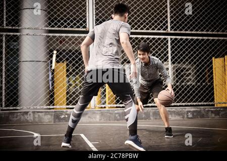 two young asian adult men playing one-on-one basketball on outdoor court - Stock Photo
