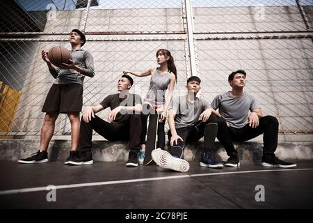 group of five asian young adults men and woman resting relaxing on outdoor basketball court - Stock Photo