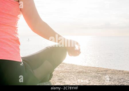 hand of an unrecognizable woman practicing yoga at dawn sitting in the lotus position in front of the sea, concept of mental health and relaxation, le