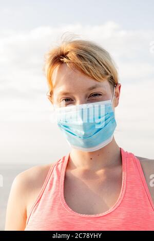 vertical portrait of a beautiful blonde woman with a protective mask with the sky in the background, concept of prevention and health care - Stock Photo