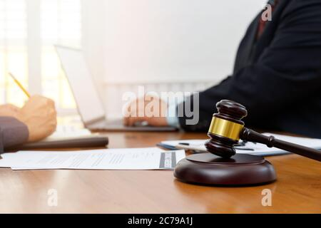 Wooden gavel on table in lawyer's office. Lawyer having team meeting with the client. Concepts of law, advice, legal services.