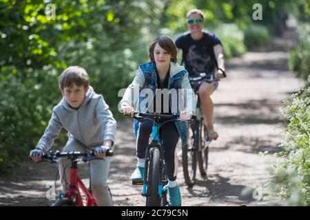 Mother and sons enjoying bike ride on sunny path - Stock Photo