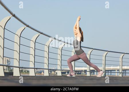 Sporty middle-aged woman with closed eyes performing warrior pose with raised arms on city embankment - Stock Photo