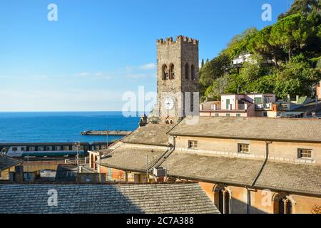 The tower of Chiesa di San Giovanni Battista with the Ligurian sea beyond as a train passes in Monterosso al Mare, Cinque Terre Italy on a sunny day Stock Photo