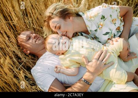 Happy young family with baby lying and resting among yellow wheat field. Closeup. - Stock Photo