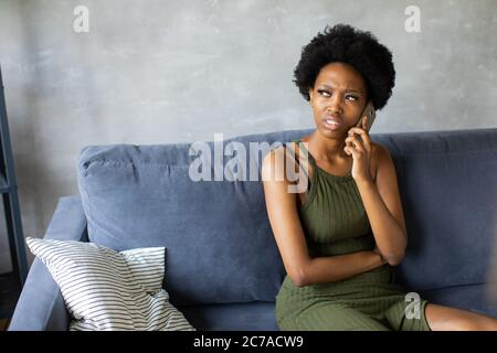 Unhappy African American woman talking on the phone, angry girl talking on the phone. - Stock Photo