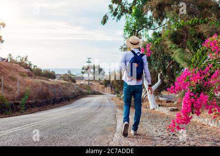 Man traveler walks along road in Akrotiri village on Santorini island Greece. Tourist backpacker admires flowers