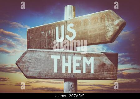 Us, them - wooden signpost, roadsign with two arrows - Stock Photo