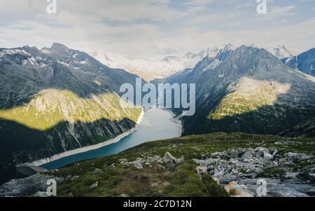 Hiking the Zillertal Alps. Olperer hut in Austria, with view on lake surrounded by high alpine mountains and stream floating down between stones. - Stock Photo