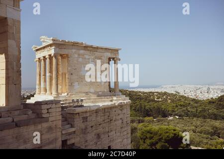 The temple of Nike on the Acropolis in Athens in Greece without people in the sunlight and blue sky with the city of Athens in background - Stock Photo