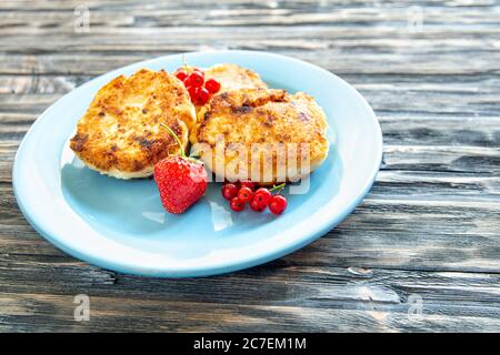 Close up delicious cottage cheese pancakes with fresh blueberries and on wooden background. Healthy breakfast concept.