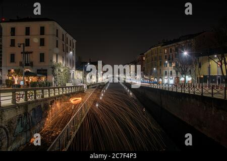A horizontal shot of beautiful steel wool effect with flames spreading on the highway at night in Milan, Italy - Stock Photo