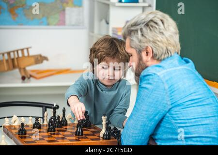 Generations men. Cute little boy playing chess with Parents. Nice concentrated little boy sitting at the table and playing chess with his father