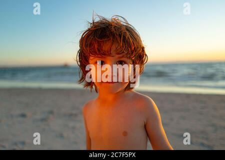 Cute little boy on the sea in summer day. Happy child on summer vacation. Travel and adventure concept. Stock Photo
