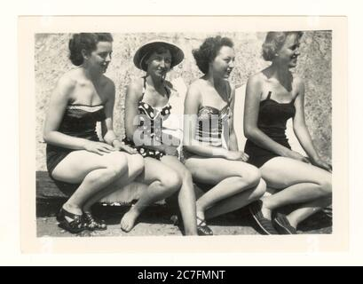 Snapshot of four attractive young women wearing fashionable swimsuits sitting on the beach, posing for a photograph together at Rhyl, Clwyd, Wales,U.K. dated July 16th 1955 - Stock Photo