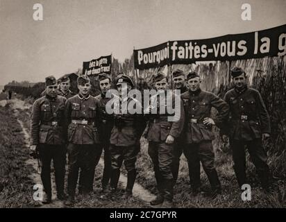 Following the Battle of France, also known as the Fall of France, the German invasion of France and the Low Countries  in the spring of 1940 during the Second World War, a group of German soldiers stand in front of propaganda posters. - Stock Photo