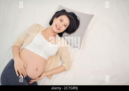 Beautiful pregnant woman laying in bed - Stock Photo