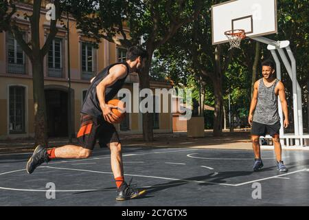 two young men play basketball outdoors - Stock Photo