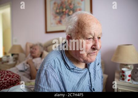 Elderly couple in their 80's sat on the bed in their pyjamas before getting up in the in the morning, England, United Kingdom - Stock Photo