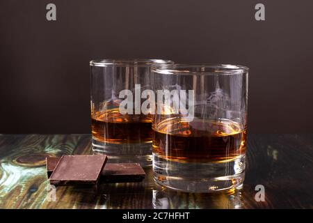 Two glasses with whiskey and pieces of dark chocolate. Appetizer for alcohol, dear spirits.