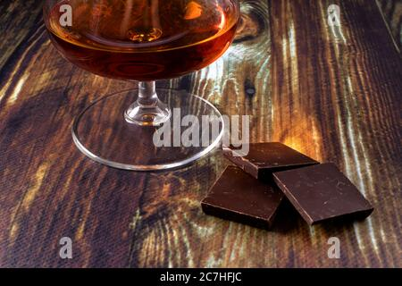 Glass with cognac and dark chocolate. Dear elite alcohol on a dark brown background. Alcoholic drinks.