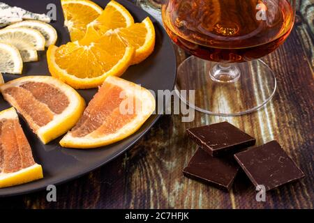 Cognac in a glass and an appetizer for cognac chocolate, lemon, orange and grapefruit. Appetizer for alcohol, dear spirits.