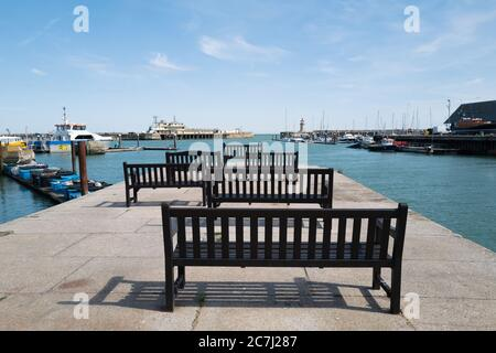 Wooden benches in the Royal Harbour, Ramsgate, looking out towards the lighthouse and an end of pier restaurant - Stock Photo