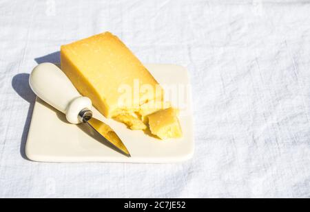 a wedge of cheddar cheese and a small knife on a cheese plate atop a white linen table cloth at a picnic with copy space - Stock Photo
