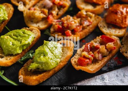 Assorted bruschetta with various toppings on a dark plate on white background. Appetizing bruschetta. - Stock Photo