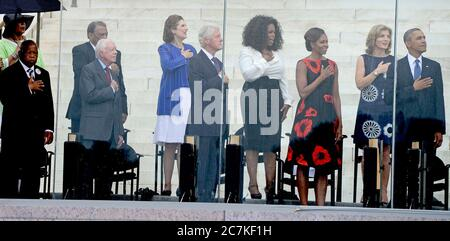 From left to right: United States Representative John Lewis (Democrat of Georgia), Ambassador Andrew Young, former U.S. President Jimmy Carter, Lynda Bird Johnson Robb, former U.S. President Bill Clinton, Oprah Winfrey, first lady Michelle Obama, Ambassador Caroline Kennedy, and United States President Barack Obama listen to the National Anthem at the Let Freedom Ring ceremony on the steps of the Lincoln Memorial to commemorate the 50th Anniversary of the March on Washington for Jobs and Freedom.Credit: Ron Sachs/CNP | usage worldwide - Stock Photo