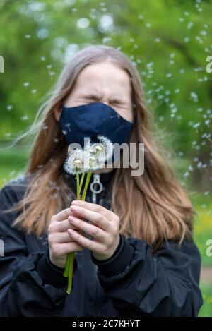 Schoolgirl with mask against corona, holding dandelions, seeds flying through the air - Stock Photo